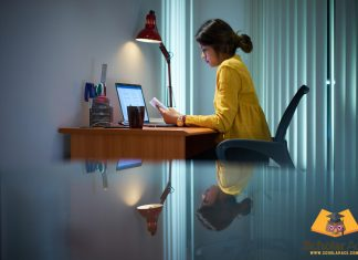 Girl writing expository essay on study desk